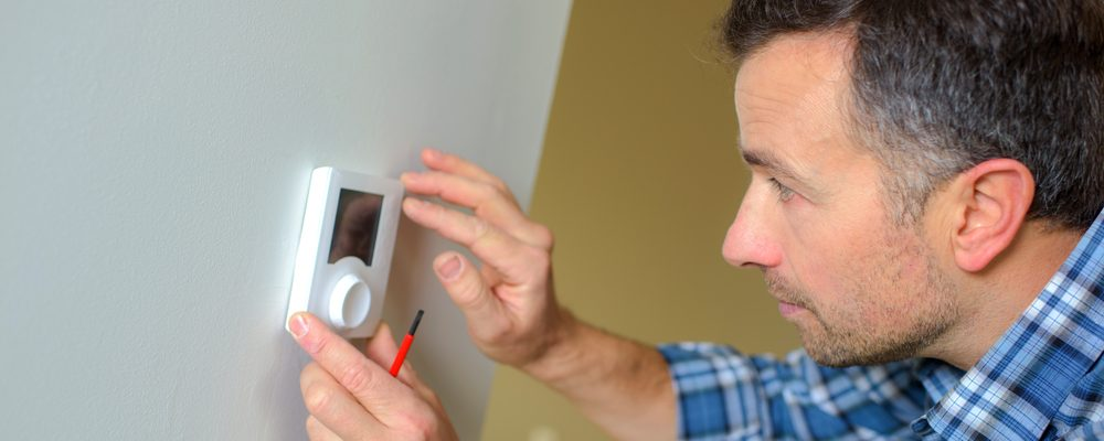 man checking the temperature of his thermostat