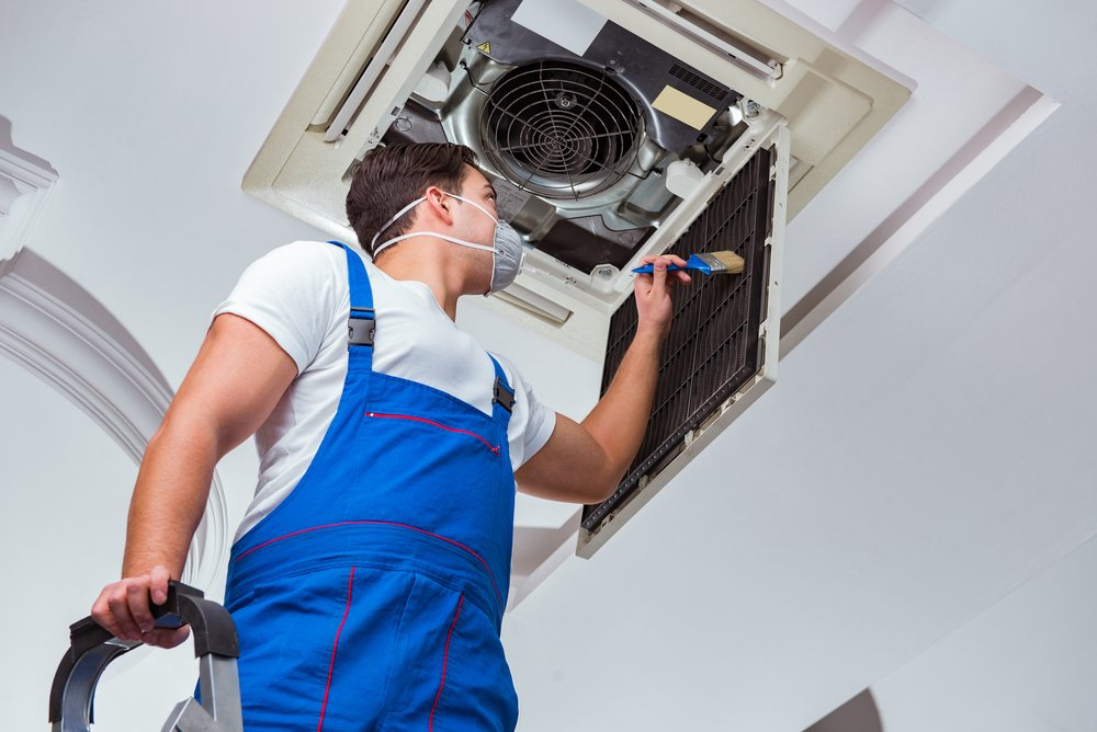 man in white shirt and blue overalls wearing a mask and dusting an air filter with a brush