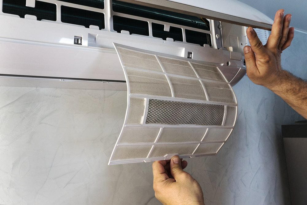 person pulling out and displaying a dirty air conditioner filter