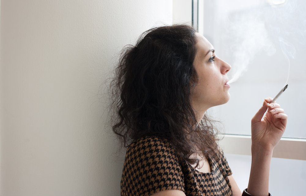 woman with black hair smoking inside while looking out of a window