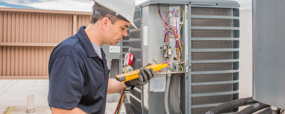 technician repairing the air condenser on an air conditioner